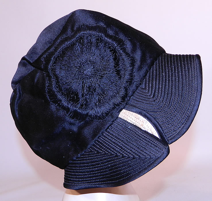 Vintage Marcelle Hats Art Deco Black  & White Silk Rosette Quilted Brim Flapper Cloche. It is made of a black silk satin fabric, with a black and white quilted stitched brim and black silk rosette embroidered applique trim on the side.