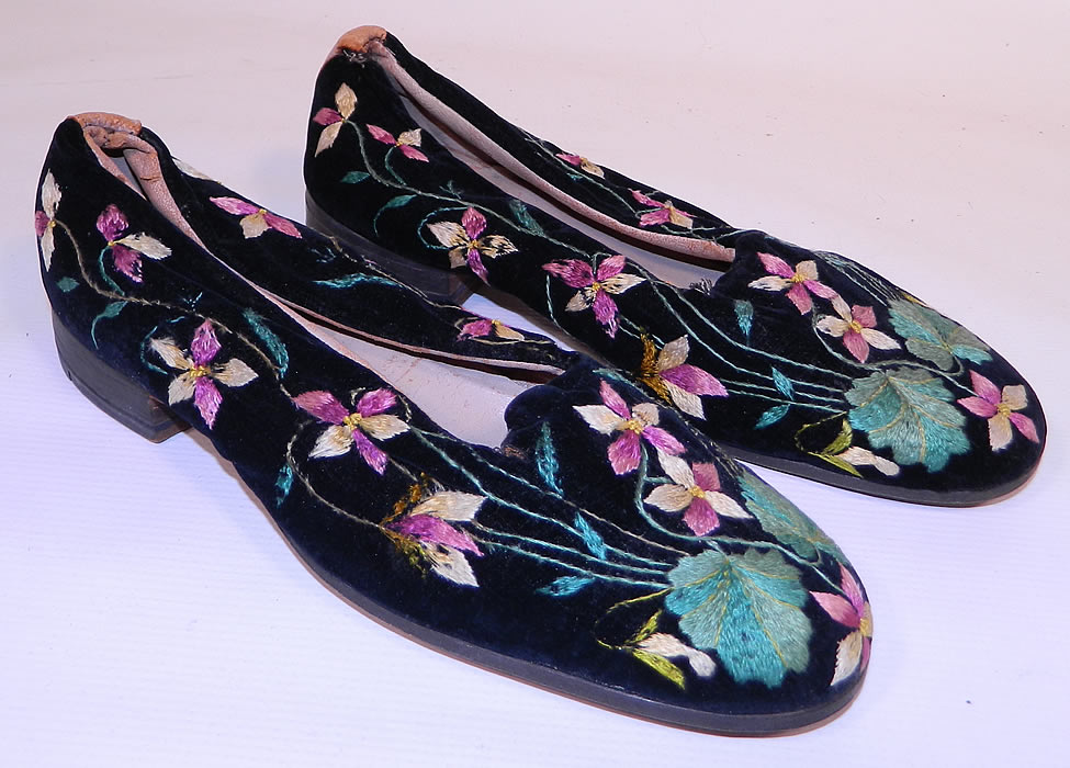 Victorian Black Velvet Violet Embroidered Men's Slipper Shoes. They are made of a black plush velvet fabric, with colorful purple violet flowers and leaves embroidered on it.